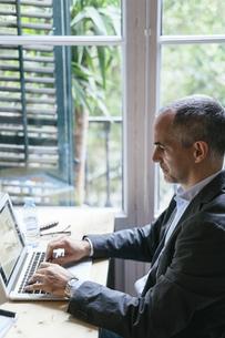 Businessman sitting at desk working on laptopの写真素材 [FYI04338171]