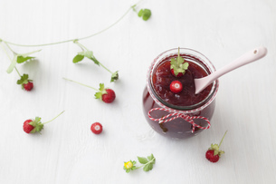 Jar of wild strawberry jam with spoon on white backgroundの写真素材 [FYI04338190]
