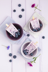 Bowl of blueberry yogurt with candy on wooden table, close uの写真素材 [FYI04338206]