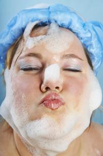Mid-adult woman wearing shower cap and bathing foamの写真素材 [FYI04338215]