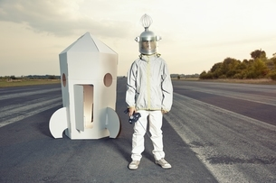 Boy dressed up as spaceman standing at cardboard rocketの写真素材 [FYI04338251]