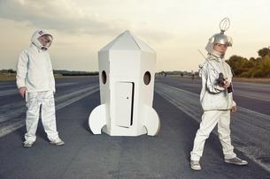 Two boys dressed up as spacemen standing at cardboard rocketの写真素材 [FYI04338256]