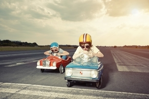 Two boys in pedal cars crossing finishing line on race trackの写真素材 [FYI04338261]