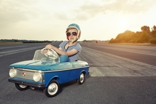 Boy with sunglasses in pedal car on race trackの写真素材 [FYI04338263]