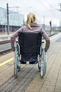 Woman in wheelchair waiting at station platformの写真素材 [FYI04338337]