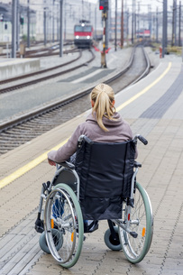 Woman in wheelchair waiting at station platformの写真素材 [FYI04338338]