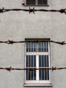 Barred window behind barbed wireの写真素材 [FYI04338352]
