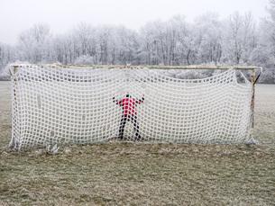 Man in soccer goal in winterの写真素材 [FYI04338357]