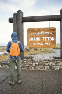 USA, Wyoming, back view of man with backpack standing at entの写真素材 [FYI04338487]