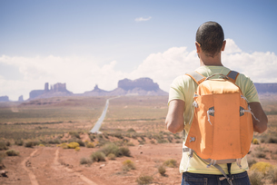 USA, Utah, back view of man with backpack looking at Monumenの写真素材 [FYI04338490]