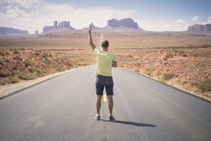 USA, Utah, back view of man standing on road to Monument Valの写真素材 [FYI04338491]