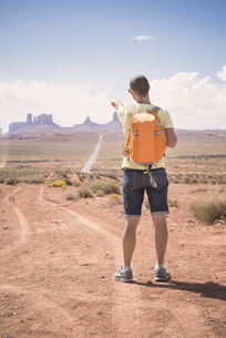 USA, Utah, back view of man with backpack pointing at Monumeの写真素材 [FYI04338494]