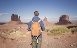 USA, Utah, back view of man with backpack looking at Monumenの写真素材 [FYI04338499]