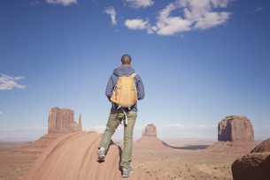 USA, Utah, back view of man with backpack looking at Monumenの写真素材 [FYI04338501]