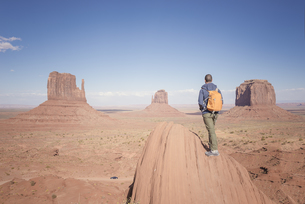 USA, Utah, back view of man with backpack looking at Monumenの写真素材 [FYI04338502]