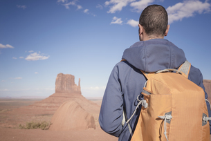 USA, Utah, back view of man with backpack looking at Monumenの写真素材 [FYI04338503]