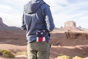 USA, Utah, back view of young man with folded American flagの写真素材 [FYI04338525]