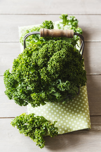 Curly kale and cloth on wooden tableの写真素材 [FYI04338569]