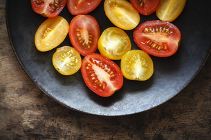 Halfed yellow and red cherry tomatoes on plateの写真素材 [FYI04338590]