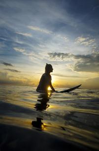 Indonesia, Bali, Canggu, silhouette of female surfer by twilの写真素材 [FYI04338606]
