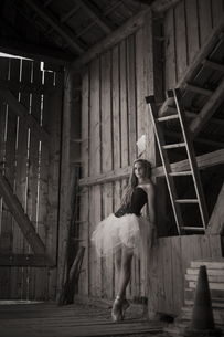 Young woman with tutu standing in barnの写真素材 [FYI04338633]