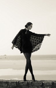 France, Bretagne, woman in black dancing on wall in front ofの写真素材 [FYI04338638]
