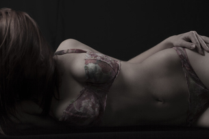 Young woman lying in front of black background wearing lingeの写真素材 [FYI04338671]