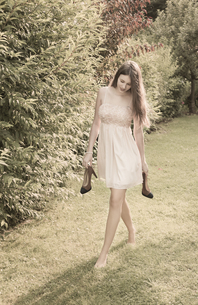 Young woman walking barefoot on meadow in the gardenの写真素材 [FYI04338683]