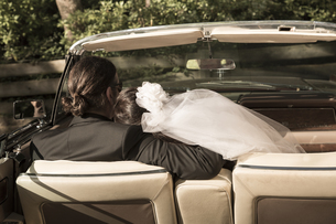 Bridal couple sitting in vintage car convertible, back viewの写真素材 [FYI04338687]