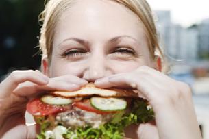 Young woman eating a hamburgerの写真素材 [FYI04338760]