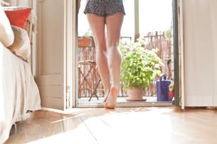 Young woman walking on her balconyの写真素材 [FYI04338791]