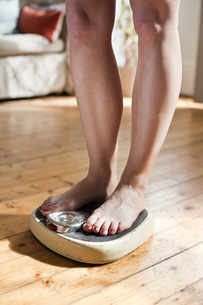 Woman standing on personal scales, partial viewの写真素材 [FYI04338793]