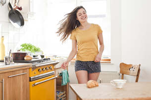 Portrait of smiling young woman dancing in her kitchenの写真素材 [FYI04338802]