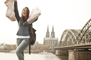 Germany, Cologne, happy young woman with shopping bagsの写真素材 [FYI04338806]