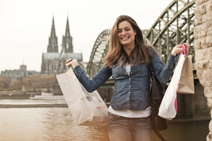 Germany, Cologne, happy young woman with shopping bags in frの写真素材 [FYI04338807]