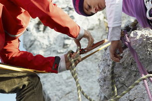 Germany, Bavaria, young couple preparing climbing ropeの写真素材 [FYI04338871]