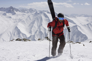 India, Kashmir, Gulmarg, Man with skis on back going uphillの写真素材 [FYI04338906]