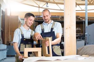 Carpenter examining work of a traineeの写真素材 [FYI04338925]