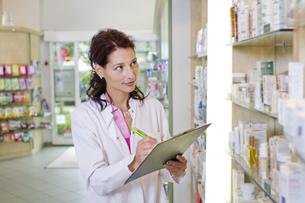 Germany, Brandenburg, Pharmacist checking products in pharmaの写真素材 [FYI04338938]