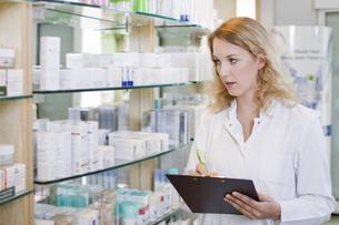 Germany, Brandenburg, Pharmacist checking products in pharmaの写真素材 [FYI04338939]
