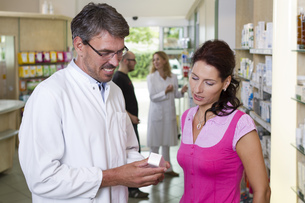 Germany, Brandenburg, Pharmacist showing medicine to womanの写真素材 [FYI04338941]