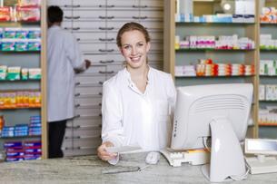 Germany, Brandenburg, Pharmacist holding prescription, smiliの写真素材 [FYI04338942]