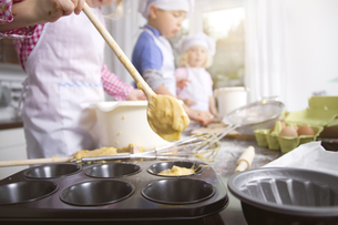 Germany, Girl filling dough in cup cake tray, boy and girl iの写真素材 [FYI04338951]