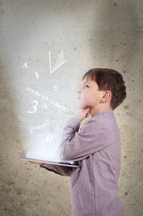 Germany, Brandenburg, Boy thinking with digital tabletの写真素材 [FYI04338963]