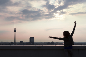 Germany, Berlin, Young woman on rooftop terrace, raising armの写真素材 [FYI04338975]