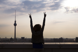 Germany, Berlin, Young woman on rooftop terrace, raising armの写真素材 [FYI04338976]