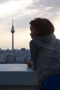 Germany, Berlin, Young woman on rooftop terrace, looking atの写真素材 [FYI04338978]