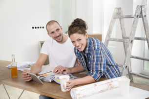 Young couple moving into new home, taking a breakの写真素材 [FYI04338984]