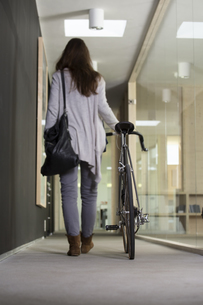 Business woman leaving office with racing cycleの写真素材 [FYI04339033]