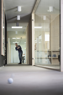 Business man playing golf in corridor of modern officeの写真素材 [FYI04339036]